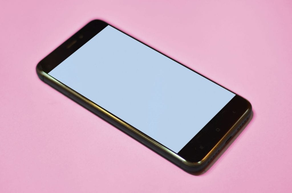 Smartphone sur fond rose